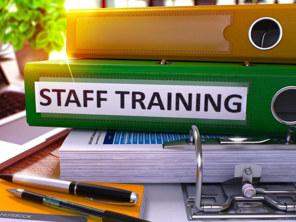 Staff Training - Green Office Folder on Background of Working Table with Stationery and Laptop. Staff Training Business Concept on Blurred Background. Staff Training Toned Image. 3D..jpeg